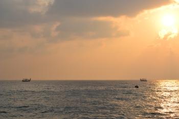 sun rising over the fishermen. pondicherry, india. march 2016.