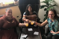 three women sitting around a table clinking their drinks together to cheer one another.