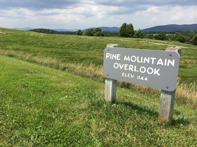 photo of a sign reading pine mountain overlook in a field.